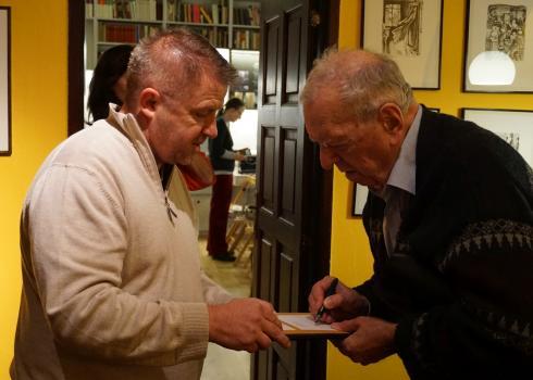 Milan Uhde (rechts) signiert sein Buch. Foto: Konstantin Kountouroyanis