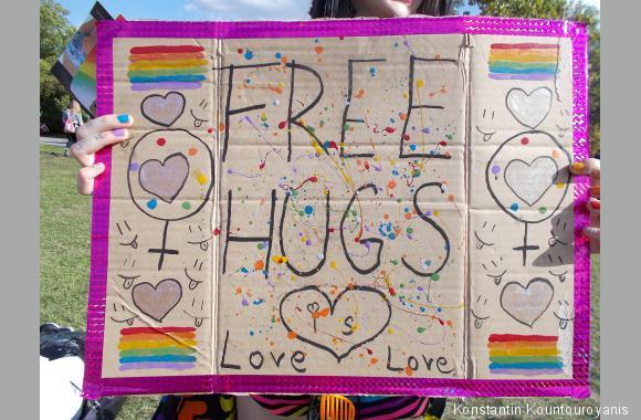 """Mehrere junge Frauen liefen mit dem Plakat """"Free Hugs"""" (""""Kostenlose Umarmungen"""") herum."""